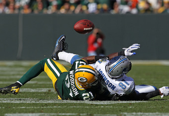 GREEN BAY, WI - OCTOBER 03: Charles Woodson #21 of the Green Bay Packers breaks up a pass intended for Calvin Johnson #81 of the Detroit Lions by taking him to the ground at Lambeau Field on October 3, 2010 in Green Bay, Wisconsin. The Packers defeated th