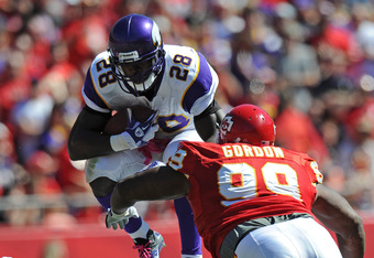 KANSAS CITY, MO - OCTOBER 02:  Running back Adrian Peterson #28 of the Minnesota Vikings leaps into the air against pressure from defensive linemen Amon Gordon #99 of the Kansas City Chiefs during the second quarter on October 2, 2011 at Arrowhead Stadium