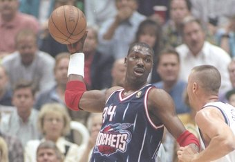 27 May 1997:  Center Hakeem Olajuwon of the Houston Rockets tries to fend off center Greg Ostertag of the Utah Jazz during a playoff game at the Delta Center in Salt Lake City, Utah.  The Jazz won the game 96-91. Mandatory Credit: Brian Bahr  /Allsport