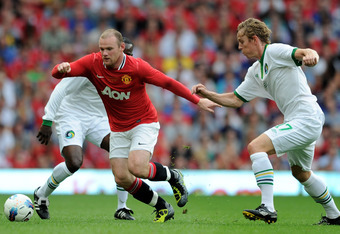 MANCHESTER, ENGLAND - AUGUST 05:  Wayne Rooney of Manchester United competes with Dane Murphy of New York Cosmos during Paul Scholes' Testimonial Match between Manchester United and New York Cosmos at Old Trafford on August 5, 2011 in Manchester, England.