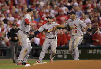 PHILADELPHIA, PA - OCTOBER 07:  (L-R) Chris Carpenter #29, Nick Punto #8 and Albert Pujols #5 of the St. Louis Cardinals celebrate after they won 1-0 against the Philadelphia Phillies during Game Five of the National League Divisional Series at Citizens B