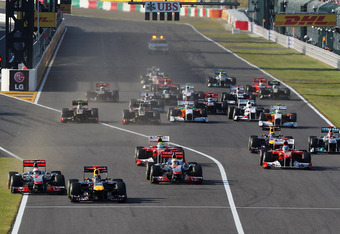 SUZUKA, JAPAN - OCTOBER 09:  Sebastian Vettel (2nd left) of Germany and Red Bull Racing leads from Jenson Button (left) of Great Britain and McLaren towards the first corner at the start of the Japanese Formula One Grand Prix at Suzuka Circuit on October