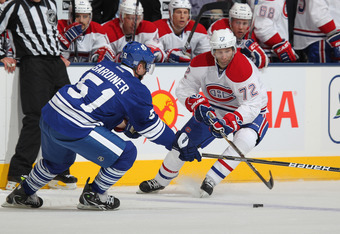 TORONTO, CANADA - OCTOBER 6:  Jake Gardiner #51 of the Toronto Maple Leafs tries to check Erik Cole #72 of the Montreal Canadiens in a game on October 6, 2011 at the Air Canada Centre in Toronto, Canada. The Leafs defeated the Canadiens 2-0. (Photo by Cla