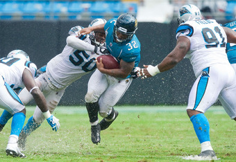Carolina Panther linebacker James Anderson (50) tackles Jacksonville Jaguar running back Maurice Jones-Drew  in Week 3 of the 2011 NFL Season.