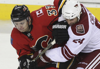 CALGARY, CANADA - SEPTEMBER 29: Anton Babchuk #33 of the Calgary Flames gets close to Kyle Chipchura #24 of the Phoenix Coyotes in third period NHL preseason action on September 29, 2011 at the Scotiabank Saddledome in Calgary, Alberta, Canada. (Photo by