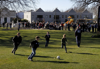 CHRISTCHURCH, NEW ZEALAND - SEPTEMBER 02:  Young children play soccer as rugby fans queue at Victoria Park band rotunda for autographs of members of the New Zealand All Blacks IRB Rugby World Cup 2011 team during a visit to Rangiora on September 2, 2011 i