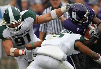 EVANSTON, IL - OCTOBER 23: Johnny Adams #5 and Tyler Hoover #91 of the Michigan State Spartans bring down Rashad Lawrence #17 of the Northwestern Wildcats at Ryan Field on October 23, 2010 in Evanston, Illinois. Michigan State defeated Northwestern 35-27.