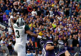 EVANSTON, IL - OCTOBER 23: B.J. Cunningham #3 of the Michigan State Spartans leaps for the ball for a touchdown catch over Brian Peters #10 of the Northwestern Wildcats at Ryan Field on October 23, 2010 in Evanston, Illinois. Michigan State defeated North