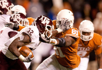 AUSTIN, TX - NOVEMBER 25:  Running back Cyrus Gray #32 of Texas A&M holds off University of Texas defensive end Sam Acho #81 during the second half at Darrell K. Royal-Texas Memorial Stadium on November 25, 2010 in Austin, Texas. (Photo by Darren Carroll/