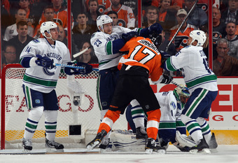 PHILADELPHIA, PA - OCTOBER 12: (L-R) Alex Burrows #14, Alexander Edler #23 and Marco Sturm #15 of the Vancouver Canucks hold off Wayne Simmonds #17 of the Philadelphia Flyers at the Wells Fargo Center on October 12, 2011 in Philadelphia, Pennsylvania.  (P
