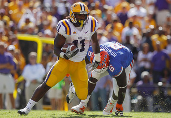 BATON ROUGE, LA - OCTOBER 08:  Spencer Ware #11 of the Louisiana State University Tigers runs past Jaye Howard #6 of the Florida Gators at Tiger Stadium on October 8, 2011 in Baton Rouge, Louisiana.  The Tigers defeated the Gators 41-11.  (Photo by Chris