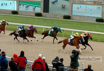 Horses storm to the finish line over Keeneland's Polytrack with state-of-the-art television screens featuring Trackus behind them.