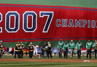 BOSTON - APRIL 08:  Past and present members of the NHL's Boston Bruins, the NBA's Boston Celtics and the NFL's New England Patriots carry the Boston Red Sox' 2007 World Series rings onto the field before the Red Sox MLB baseball game against the Detroit