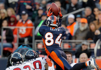 DENVER - DECEMBER 26:  Wide receiver Brandon Lloyd #84 of the Denver Broncos makes a leaping catch for a 41-yard reception against corner back Jason Allen #30 and safety Troy Nolan #33 of the Houston Texans during the third quarter at INVESCO Field at Mil