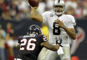 HOUSTON - OCTOBER 09:  Quarterback Jason Campbell #8 of the Oakland Raiders is pressured by cornerback Brandon Norris #26 of the Houston Texans at Reliant Stadium on October 9, 2011 in Houston, Texas.  (Photo by Bob Levey/Getty Images)