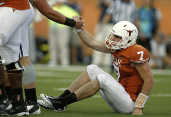 AUSTIN, TX Ð SEPTEMBER 10:  Quarterback Garrett Gilbert #7 of the Texas Longhorns is helped up after being sacked in the second quarter against the BYU Cougars on September 10, 2011 at Darrell K. Royal-Texas Memorial Stadium in Austin, Texas.  Texas defea