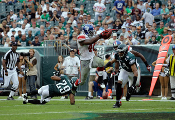 PHILADELPHIA, PA - SEPTEMBER 25:  Running back  Ahmad Bradshaw #44 of the New York Giants jumps over defenders Nate Allen #29 and Nnamdi Asomugha #24 of the Philadelphia Eagles for a touchdown in the fourth quarter at Lincoln Financial Field on September