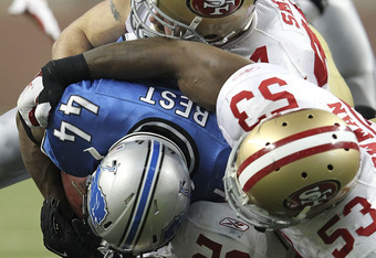DETROIT - OCTOBER 16: Patrick Willis #52, NaVorro Bowman #53 and Justin Smith #94 of the San Francisco 49ers tackle Jahvid Best #44 of the Detroit Lions during the second quarter of the NFL game at Ford Field on October 16, 2011 in Detroit, Michigan. The