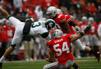 COLUMBUS, OH - OCTOBER 1:  John Simon #54 of the Ohio State Buckeyes hits Mike Sadler #3 of the Michigan State Spartans after Sadler fumbled a punt on October 1, 2011 at Ohio Stadium in Columbus, Ohio. (Photo by Kirk Irwin/Getty Images)