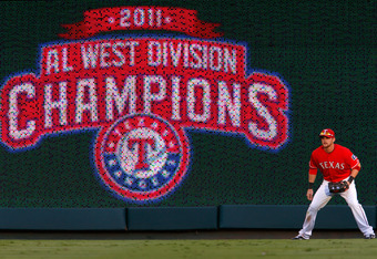 ARLINGTON, TX - SEPTEMBER 30:  Outfielder Craig Gentry #23 of the Texas Rangers stands in the outfield next to the board displaying '2011 Al West Division Champions' while taking on the Tampa Bay Rays during Game One of the American League Division Series