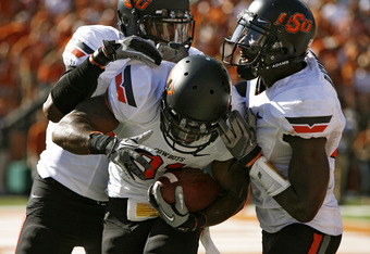 AUSTIN, TX - OCTOBER 15:  Running back Jeremy Smith #31, center,  of the Oklahoma State University Cowboys is congratulated by tight end Wilson Youman #86, left, and wide receiver Justin Blackmon #81, right, after running in a second quarter touchdown aga