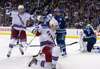 VANCOUVER, CANADA - OCTOBER 18: Ryan McDonagh #27 of the New York Rangers celebrates after scoring against goalie Roberto Luongo #1 of the Vancouver Canucks as Artem Anisimov #42 and Ryan Callahan #24 of the Rangers celebrate and Dan Hamhuis #2 of the Can