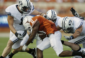 AUSTIN, TX - SEPTEMBER 10:  Running back Fozzy Whittaker #2 of the Texas Longhorns is tackled in the first quarter by linebacker Jordan Pendleton #1, defensive back Daniel Sorensen #9, and linebacker Uona Kaveinga #4 of the BYU Cougars on September 10, 20