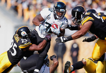 PITTSBURGH, PA - OCTOBER 16:  Maurice Jones-Drew #32 of the Jacksonville Jaguars tries to split the tackles of Cameron Heyward #97 and Ryan Clark #25 of the Pittsburgh Steelers during a third quarter run at Heinz Field on October 16, 2011 in Pittsburgh, P