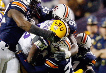 BATON ROUGE, LA - OCTOBER 24:  Terrance Toliver #80 of the Louisiana State University Tigers is tackled by Daren Bates #25 of the Auburn Tigers at Tiger Stadium on October 24, 2009 in Baton Rouge, Louisiana.  (Photo by Chris Graythen/Getty Images)