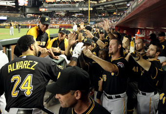 PHOENIX, AZ - SEPTEMBER 20:  Pedro Alvarez #24 of the Pittsburgh Pirates celebrates with teammates in the dugout after hitting a solo home run against the Arizona Diamondbacks during the second inning of the Major League Baseball game at Chase Field on Se