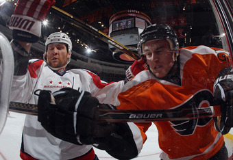 PHILADELPHIA, PA - OCTOBER 20: Dennis Wideman #6 of the Washington Capitals checks Matt Read #24 of the Philadelphia Flyers into the glass during the second period at the Wells Fargo Center on October 20, 2011 in Philadelphia, Pennsylvania.  (Photo by Bru