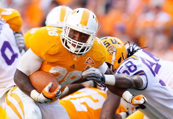 KNOXVILLE, TN - OCTOBER 15:  Tauren Poole #28 of the Tennessee Volunteers tries to break a tackle by Tahj Jones #58 of the LSU Tigers at Neyland Stadium on October 15, 2011 in Knoxville, Tennessee.  (Photo by Kevin C. Cox/Getty Images)
