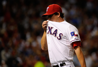 ARLINGTON, TX - OCTOBER 15:  Derek Holland #45 of the Texas Rangers walks off the field in the first inning of Game Six of the American League Championship Series against the Detroit Tigers at Rangers Ballpark in Arlington on October 15, 2011 in Arlington