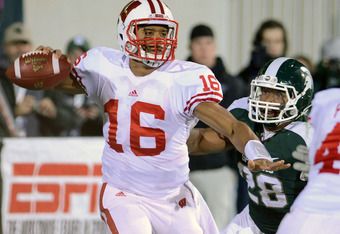EAST LANSING, MI - OCTOBER 22:  Russell Wilson #16 of the Wisconsin Badgers looks to pass while under pressure from Denicos Allen #28 of the Michigan State Spartans during the second quarter of the game at Spartan Stadium on October 22, 2011 in East Lansi
