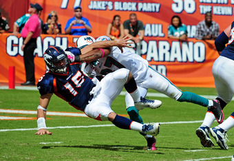 MIAMI GARDENS, FL - OCTOBER 23: Tim Tebow #15 of the Denver Broncos is pressured by Yeremiah Bell #37 of the Miami Dolphins at Sun Life Stadium on October 23, 2011 in Miami Gardens, Florida. (Photo by Scott Cunningham/Getty Images)