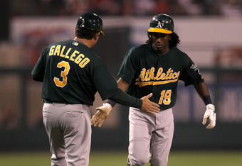 ANAHEIM, CA - SEPTEMBER 23:  Jemile Weeks #19 of the Oakland Athletics is greeted by third base coach Mike Gallego as he rounds third base after hitting a home run to lead off the game against the Los Angeles Angels of Anaheim on September 23, 2011 at Ang