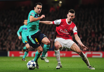 LONDON, ENGLAND - FEBRUARY 16:  Laurent Koscielny of Arsenal challenges Xavi Hernandez of Barcelona during the UEFA Champions League round of 16 first leg match between Arsenal and Barcelona at the Emirates Stadium on February 16, 2011 in London, England.