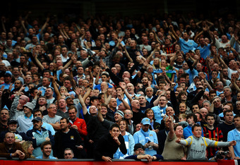 MANCHESTER, ENGLAND - OCTOBER 23: Manchester City fans celebrate during the Barclays Premier League match between Manchester United and Manchester City at Old Trafford on October 23, 2011 in Manchester, England. (Photo by Laurence Griffiths/Getty Images)