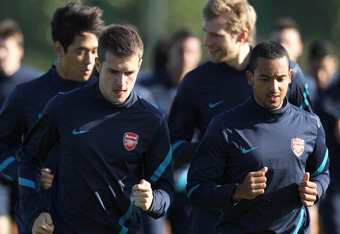 ST ALBANS, ENGLAND - OCTOBER 18 :   Aaron Ramsey (L), Theo Walcott and Arsenal team-mates jog during a training session ahead of their UEFA Champions League Group F match against Olympique de Marseille at London Colney on October 18, 2011 in St Albans, En
