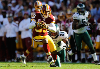 LANDOVER, MD - OCTOBER 16:  Santana Moss #89 of the Washington Redskins avoids a tackle by  Ronnie Brown #21 of the Philadelphia Eagles during a game at FedExField on October 16, 2011 in Landover, Maryland.  (Photo by Patrick McDermott/Getty Images)
