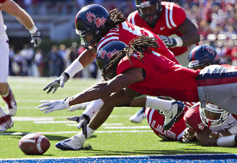 OXFORD,  MS - OCTOBER 22:  Charles Sawyer #3 and Frank Crawford #5 of the Ole Miss Rebels dive on a fumble at the goal line during a game against the Arkansas Razorbacks at Vaught-Hemingway Stadium on October 22, 2011 in Oxford, Mississippi.  The Razorbac