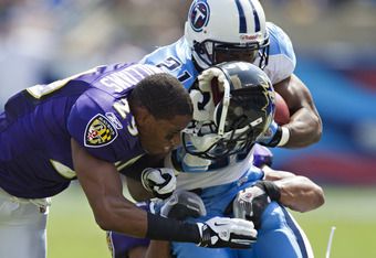NASHVILLE, TN - SEPTEMBER 18:   Cary  Williams #29 of the Baltimore Ravens loses his helmet while making a hit on Javon Ringer #21 of the Tennessee Titans at the LP Field on September 18, 2011 in Nashville, Tennessee.  (Photo by Wesley Hitt/Getty Images)
