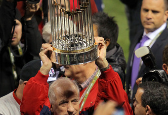 ST LOUIS, MO - OCTOBER 28:   Mike Bertani, director of stadium operations of the St. Louis Cardinals celebrates with the World Series trophy after defeating the Texas Rangers 6-2 in Game Seven of the MLB World Series at Busch Stadium on October 28, 2011 i