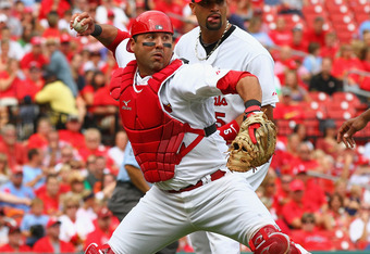 ST. LOUIS, MO -SEPTEMBER 4: Gerald Laird #13 of the St. Louis Cardinals throws to first base as teammates Albert Pujols #5 and Edwin Jackson #22 look on against the Cincinnati Reds at Busch Stadium on September 4, 2011 in St. Louis, Missouri.  The Reds be