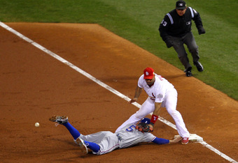 ST LOUIS, MO - OCTOBER 28:  Ian Kinsler #5 of the Texas Rangers is safe at first base after an error by Albert Pujols #5 of the St. Louis Cardinals in the second inning during Game Seven of the MLB World Series at Busch Stadium on October 28, 2011 in St L