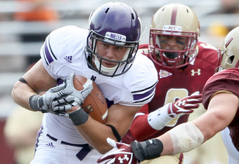 CHESTNUT HILL, MA - SEPTEMBER 03:  Mike Trumpy #29 of the Northwestern Wildcats carries the ball as Dominique Williams #9 of the Boston College Eagles defends on September 3, 2011 at Alumni Stadium in Chestnut Hill, Massachusetts.The Northwestern Wildcats