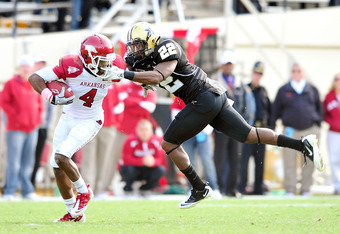 NASHVILLE, TN - OCTOBER 29:  Eric Samuels #22 of the Vanderbilt Commodores draws a facemask penalty as he tackles Jarius Wright #4 of the Arkansas Razorbacks during play at Vanderbilt Stadium on October 29, 2011 in Nashville, Tennessee. Arkansas won 31-28