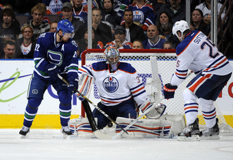 EDMONTON, CANADA - OCTOBER 25: Nikolai Khabibulin #35 of the Edmonton Oilers stops a deflection by Daniel Sedin #22  of the Vancouver Canucks on October 25, 2011 at the Rexall Place in Edmonton, Alberta, Canada. (Photo by Dale MacMillan/Getty Images)