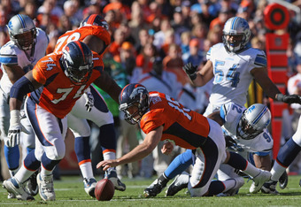 DENVER, CO - OCTOBER 30:  Quarterback Tim Tebow #15 of the Denver Broncos recovers his fumble after being sacked by Cliff Avril #92 of the Detroit Lions at Sports Authority at Invesco Field at Mile High on October 30, 2011 in Denver, Colorado. The Lions d