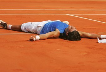 PARIS - JUNE 11:  Rafael Nadal of Spain lies on the clay after defeating Roger Federer of Switzerland during the Men's Singles Final on day fifteen of the French Open at Roland Garros on June 11, 2006 in Paris, France.  (Photo by Matthew Stockman/Getty Im